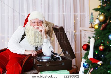 Santa Claus sitting in comfortable chair near retro turntable at home