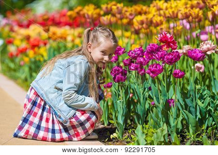 Little adorable girl smelling colorful tulips at summer day