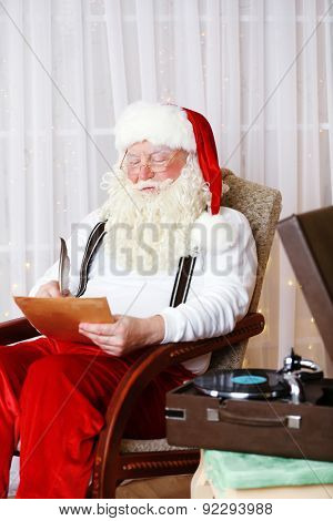 Santa Claus sitting with list of children wishes in comfortable chair at home