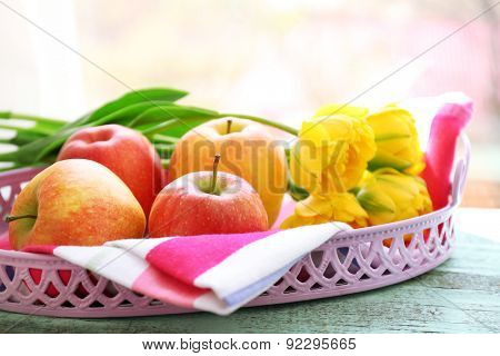 Beautiful bouquet of tulips with fruits on metal tray on windowsill