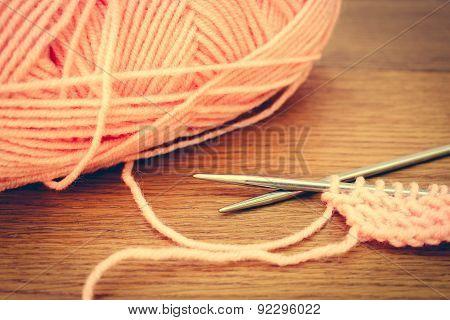 beige yarns and knitting needles. Toned image.