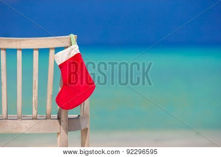 Red Christmas stocking on chair  at outdoor cafe background the sea