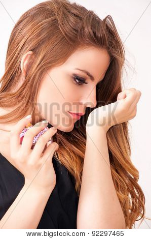 Teenage girl holding bottle of a perfume and smelling her hand