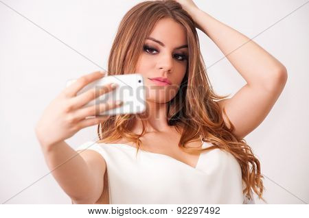 Beautiful teenage girl with curly hair, taking selfie with white mobile