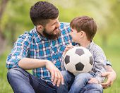 stock photo of football pitch  - Young father with his little son having fun on football pitch - JPG