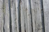 picture of log fence  - Old fence from dingy planks - JPG