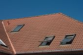 stock photo of red roof  - Red tile roof with windows and clear sky - JPG