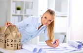 pic of blueprints  - Portrait of female architect with blueprints at desk in office - JPG