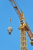 stock photo of girder  - Crane lifting concrete mixer container against blue sky - JPG