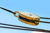 stock photo of pulley  - pulley with ropes from an ancient sailing vessel against the blue summer sky copy space in the background - JPG