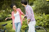 foto of tandem bicycle  - Young couple with a bicycle in a park - JPG