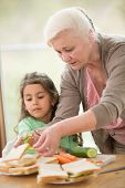 picture of grandmother  - Girl looking at grandmother preparing sandwiches at home - JPG