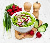 pic of radish  - Spring salad with cucumbers and radish on a wooden background - JPG