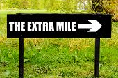 Постер, плакат: The Extra Mile Written On Directional Black Metal Sign
