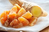 picture of rhizomes  - Closeup dried candied crystallized ginger pieces and fresh rhizome root on rustic table - JPG