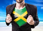 pic of rastafari  - Businessman stretching suit with Jamaica Flag on beach background - JPG