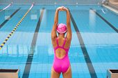 stock photo of stretch  - Young sportswoman stretching and preparing to swimming - JPG