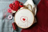 picture of sewing  - The embroidery hoop with canvas and red sewing threads on table close up - JPG