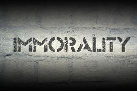 stock photo of debauchery  - immorality stencil print on the grunge white brick wall - JPG