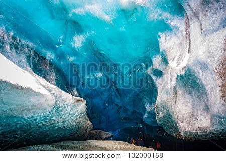 An amazing glacial ice cave entrance with travelers in Iceland