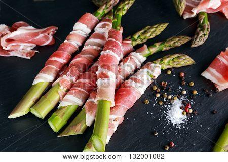 Fresh Organic raw Bacon Wrapped Asparagus on stone background.