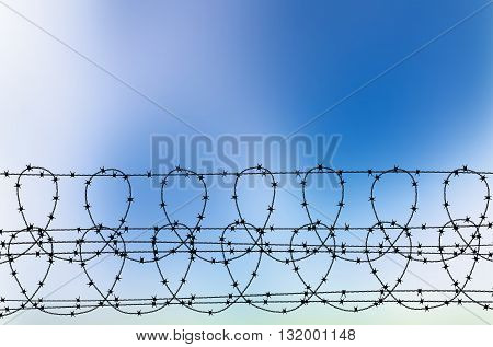 Vector illustration of barbed wire against blue sky. Abstract blurred sky background with barbed wire. Silhouette of barbed wire - blue sky background. Place for your text above barbed wire.
