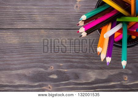 Color pencils in black office bin on dark wooden background