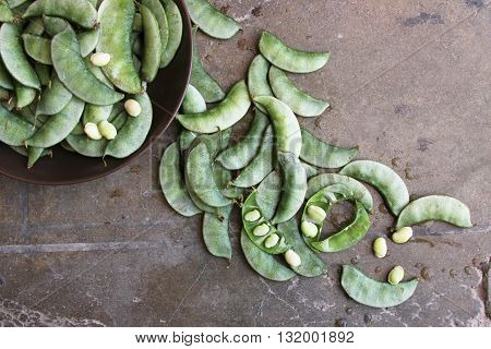 Overhead of whole raw green bean pods in a bowl and scattered with beans