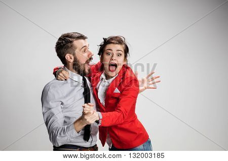 The funny business man and woman laughing on a gray background. Business concept of relationship and victory