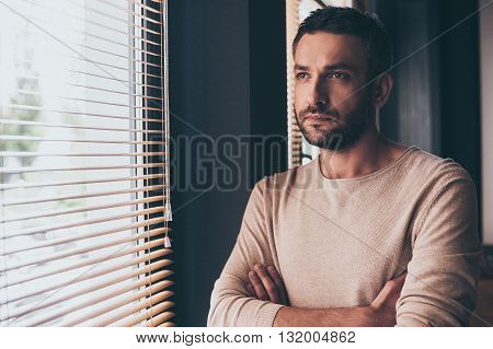 Handsome and thoughtful. Handsome young man looking trough window while standing at his working place