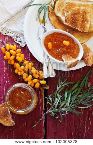 Homemade sea buckthorn jam toast and ripe sea buckthorn berries on the table. Healthy breakfast.Top view . Bio healthy food