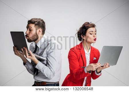 Love on the Internet. The young businessman and businesswoman with laptops kissing screens on gray background