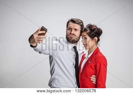 Two colleagues friends taking the picture to them self posing in the office, man and woman taking selfie with telephone camera, working funny in the office on gray background
