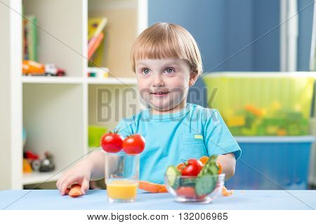 Cutechild boy eats carrot and other vegetables in room