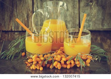 Homemade sea buckthorn soft drink in a glass and ripe sea buckthorn berries on the table. Healthy and diet food. Tinted image of vintage style. Selective focus