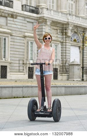 young attractive tourist woman with red hair wearing shorts and summer singlet riding happy electrical segway having fun driving in touristic city tour in Madrid royal palace in Spain