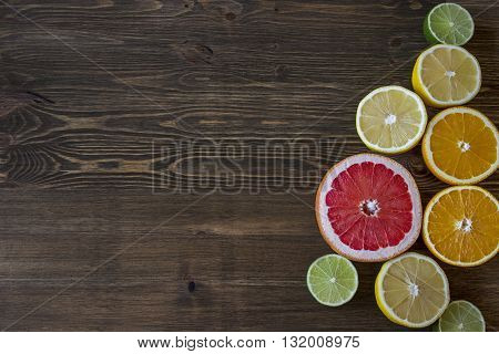Citrus fruits. Oranges, limes, grapefruit and lemons. Over wood table background with copy space