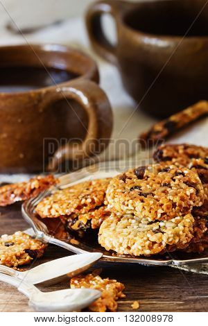 Homemade cookies from sesame seeds raisins and caramel on the old wooden background. Selective focus. Toned image
