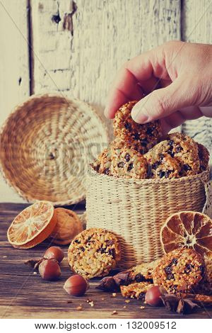 Homemade cookies from sesame seeds raisins and caramel in a basket on a wooden table. Tinted image. Selective focus