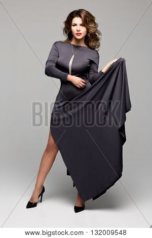 Gorgeous young woman advertises evening long dress. Volume hair, beautiful hair. The Studio, grey background
