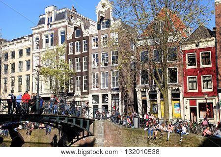 AMSTERDAM, NETHERLANDS - MAY 5, 2016: Young people relax along a canal in famous red light neighborhood in Amsterdam, Netherlands. Amsterdam is the capital and most populous city of the Netherlands