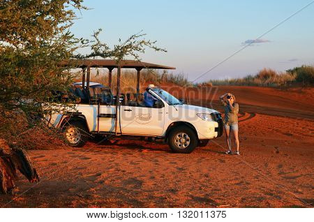 KALAHARI NAMIBIA - JAN 23 2016: Unidentified woman photographer take a pictures near offroad car in the Kalahari desert at sunset. Self drive safari most popular in Namibia between tourist