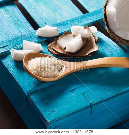 Half coconut with wedges of coconut and shreds on bright blue wooden background. Square image