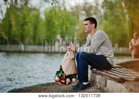 Man with a bouquet of flowers waiting for his girlfriend. Declaration of love and marriage proposal