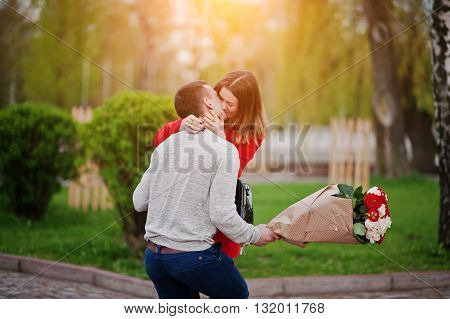 Marriage Proposal. Kissed Girl And Boyfriend With Bouquet Of Flowers