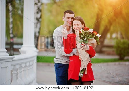 Marriage Proposal. Girl With Bouquet Of Rose Showing Her Engagement Ring At Finger