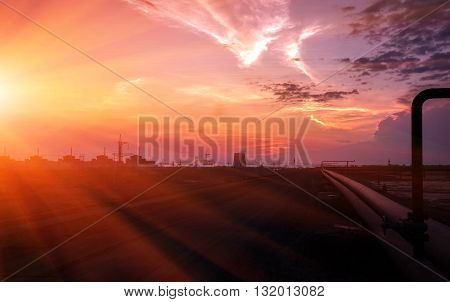 industrial background with pipes against a red sunset.