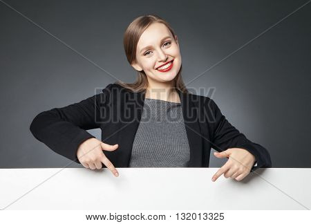 Portrait of beautiful young woman with red lips showing blank space with index finger