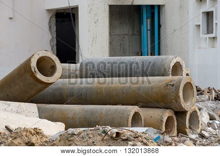 Multiple concrete pipes in front of a building at a construction site. Building and engineering concept.