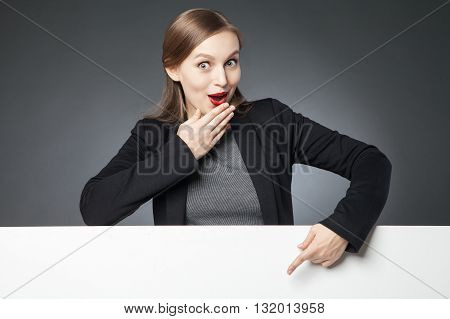 Wide-eyed woman with red lips in jacket showing blank space with index finger